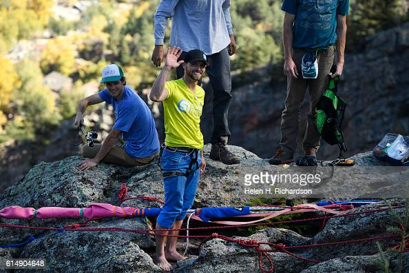 Taylor Van Allen middle waves after making the FA or First Across on a highline from the Wind Tower rock formation to the Bastille rock formation in...