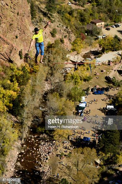 Taylor VanAllen makes the FA or First Across high above Eldorado Canyon on a highline from the Wind Tower rock formation to the Bastille rock...