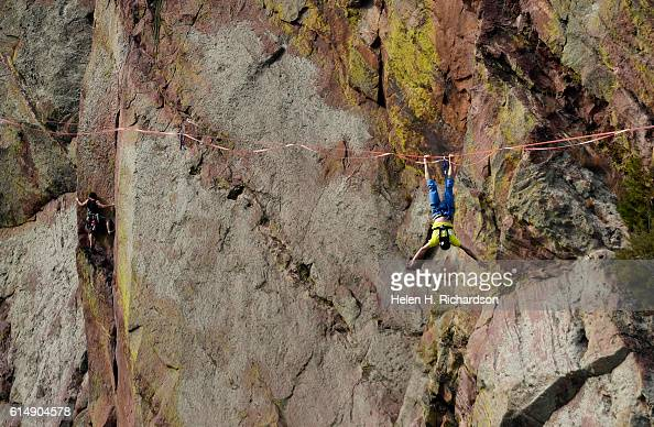 Taylor VanAllen right does tricks on his high line high above a rock climber to the left after making the FA or First Across on a highline from the...