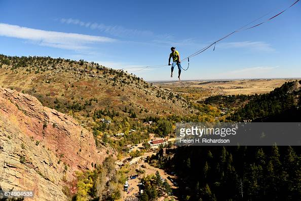 Taylor VanAllen works his way down the rope to walk on a highline from the Wind Tower rock formation to the Bastille rock formation in Eldorado...