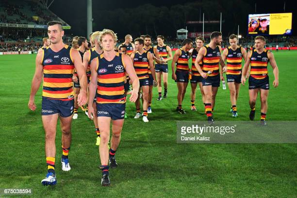 Taylor Walker and Rory Sloane of the Crows lead the Crows from the ground after defeating the Tigers during the round six AFL match between the...