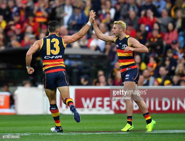 Taylor Walker congratulates Rory Atkins of the Crows during the round six AFL match between the Adelaide Crows and the Richmond Tigers at Adelaide...
