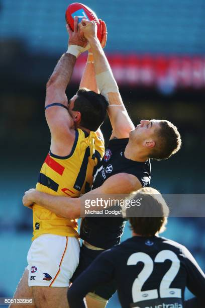 Taylor Walker of the Crows and Liam Jones of the Blues compete for the ball during the round 15 AFL match between the Carlton Blues and the Adelaide...