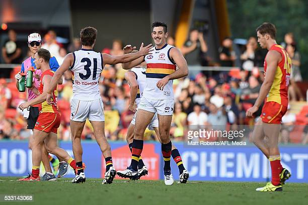 Taylor Walker of the Crows celebrates kicking a goal with team mates during the round nine AFL match between the Gold Coast Suns and the Adelaide...