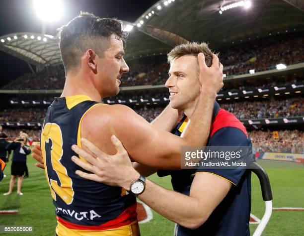 Taylor Walker of the Crows consoles an injured Brodie Smith of the Crows who will miss the grand final during the 2017 AFL First Preliminary Final...