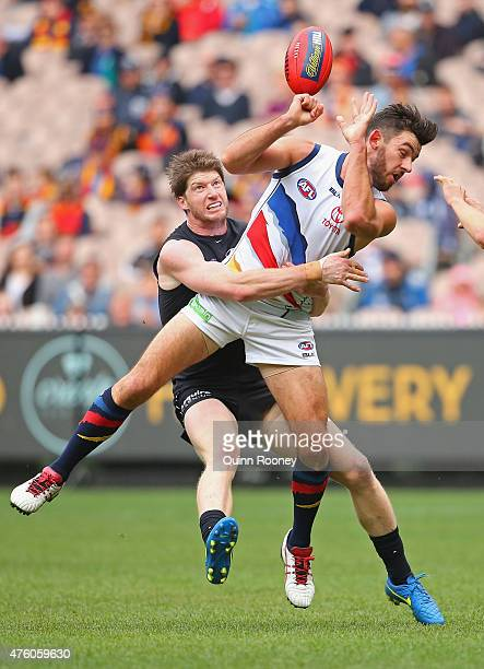 Taylor Walker of the Crows handballs whilst being tackled by Sam Rowe of the Blues during the round 10 AFL match between the Carlton Blues and the...