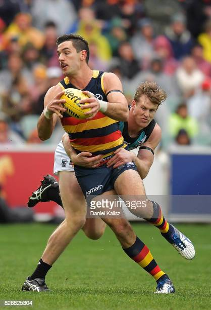 Taylor Walker of the Crows is tackled by Jack Hombsch of the Power during the round 20 AFL match between the Adelaide Crows and the Port Adelaide...