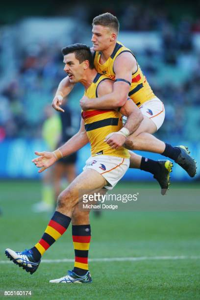 Taylor Walker of the Crows kicks the ball for a goal and celebrates with Rory Laird during the round 15 AFL match between the Carlton Blues and the...