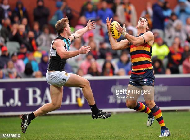 Taylor Walker of the Crows marks the ball from Tom Jonas of the Power during the round 20 AFL match between the Adelaide Crows and the Port Adelaide...