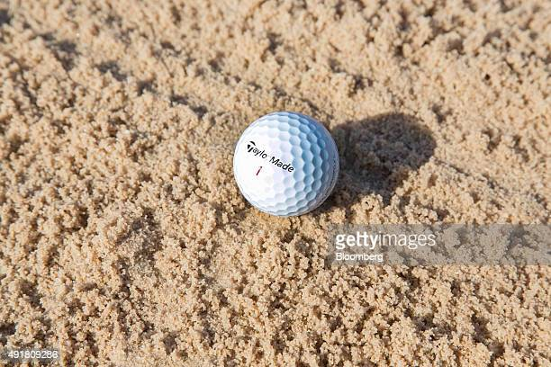 A TaylorMade Tour Preferred X golf ball rests in the sand of a bunker on the golf course at the TaylorMade center of excellence operated by Adidas AG...