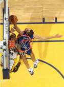 Tayshaun Prince of the Detroit Pistons blocks a shot attempt by Reggie Miller of the Indiana Pacers in the final minutes of the 4th quarter to help...