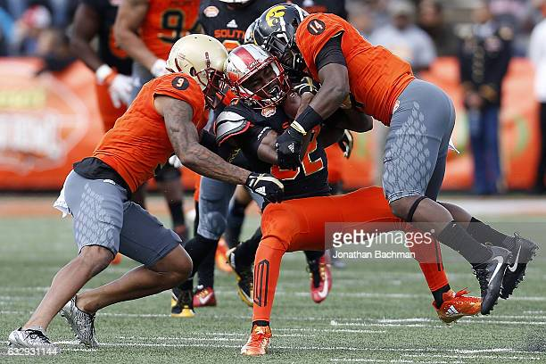Taywan Taylor of the South team is tackled by John Johnson of the North team and Desmond King during the first half of the Reese's Senior Bowl at the...