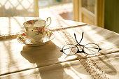 Occhiali, tazza e luce dalla finestra
