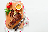 T-bone beef stake served on a cutting board, view from above, space for a text