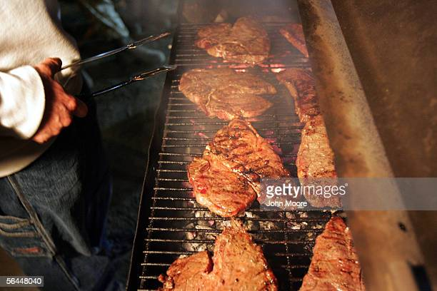 Tbone steaks cook on the grill at the US Embassy during a Christmas party for Embassy staff and US soldiers December 17 2005 in the high security...