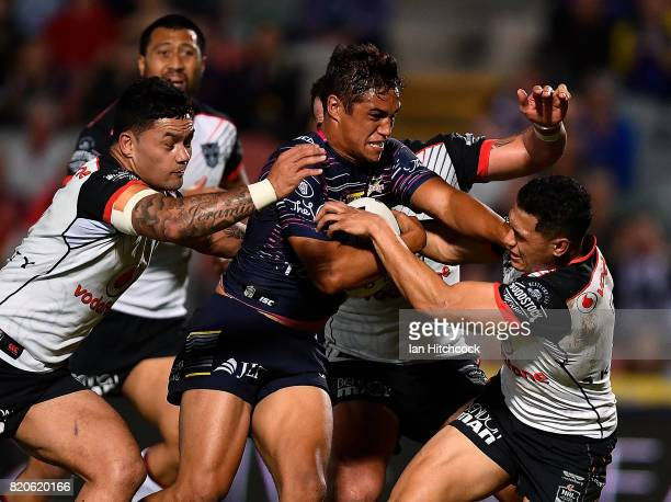 Te Maire Martin of the Cowboys is tackled by Issac Luke and Roger TuivasaSheck of the Warriors during the round 20 NRL match between the North...