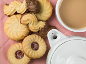 Tea and a Selection of Biscuits With a Teapot Against a Pink Background