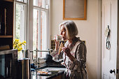 Senior woman is standing alone in her kitchen in her dressing gown, eating toast and dirnking tea.