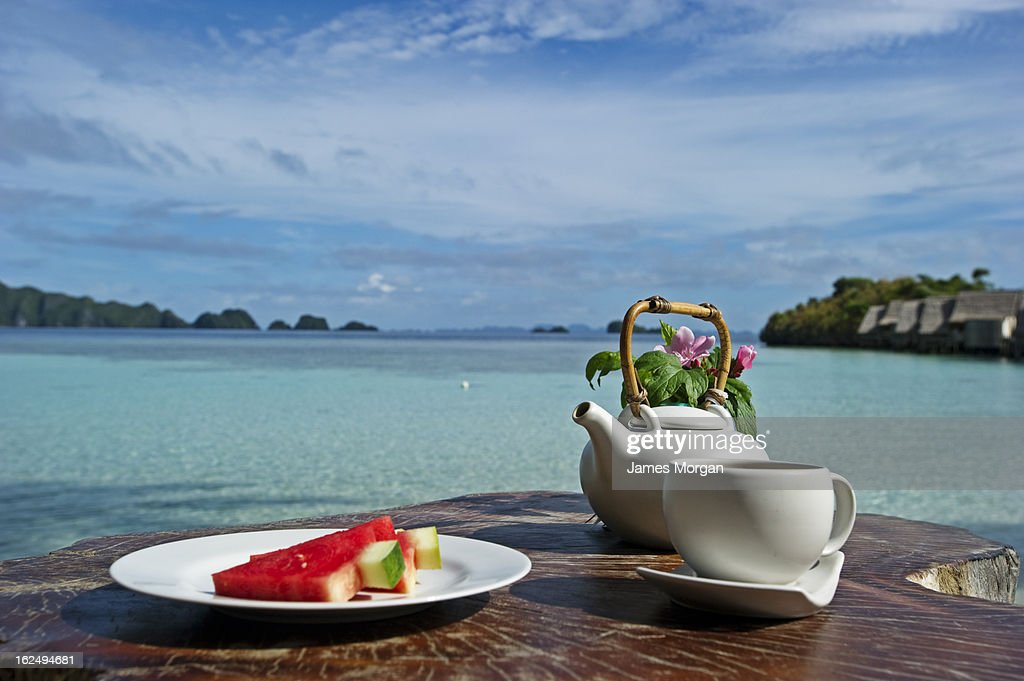 Tea and watermelon in sun with sea behind : Stock Photo