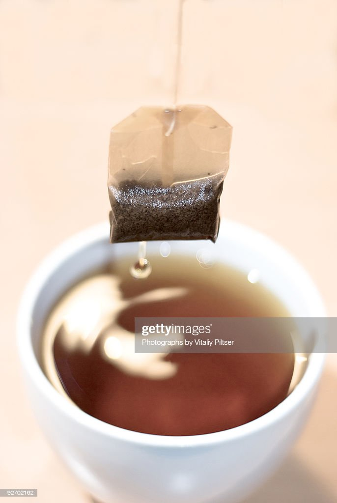 Tea bag hovering and dripping tea into cup.