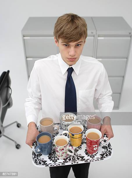 Tea boy holding a tray of prepared drinks