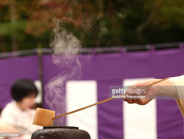 A tea ceremony master uses the Hishaku made of bamboo and makes a tea during the outdoor tea ceremony at Zuihoji Temple Park on November 3 2011 in...