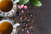 two cups of tea, tea leaves and dry rose flowers on slate