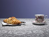 Tea cup and croissant on table