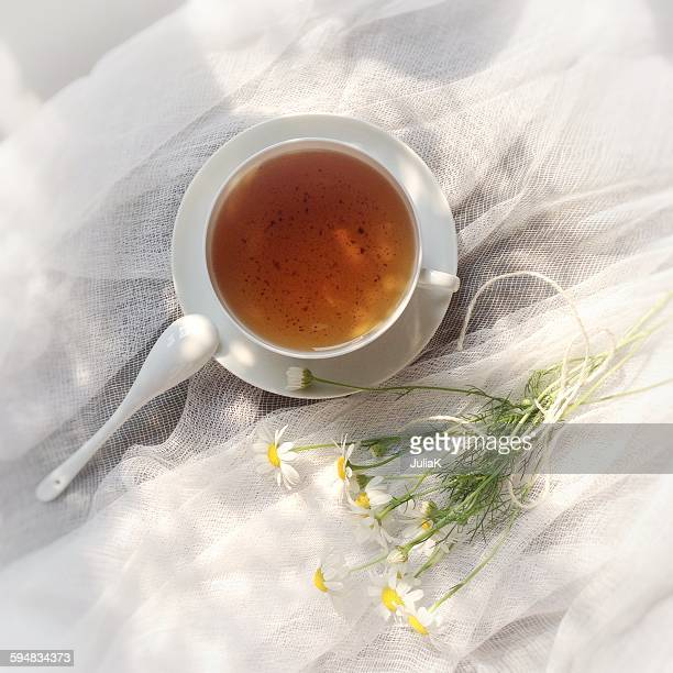 Tea cup and daisies on muslin