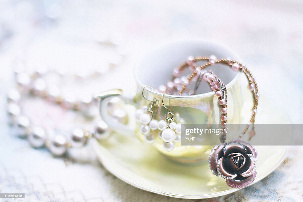 Tea cup and jewelry : Stock Photo