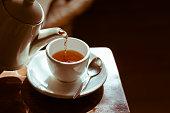 Pouring hot tea into white ceramic tea cup the time of tea break.