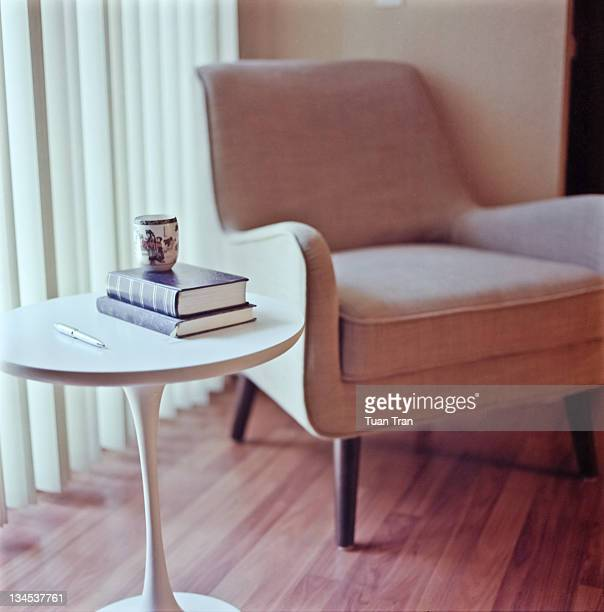Tea cup, pen and books on table