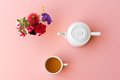 Directly above view of tea with white teapot and colourful flowers on pink background