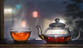 Tea cup with tea pot on the windowsill. Tea on a background of a night landscape. Tea time.