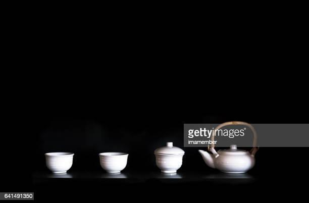 Tea cups and tea pot against black background, copy space