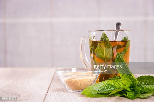 Tea glass of fresh peppermint tea and glass bowl with cane sugar