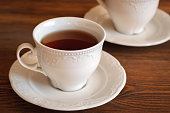 Black tea in an elegant teacup on a wooden table