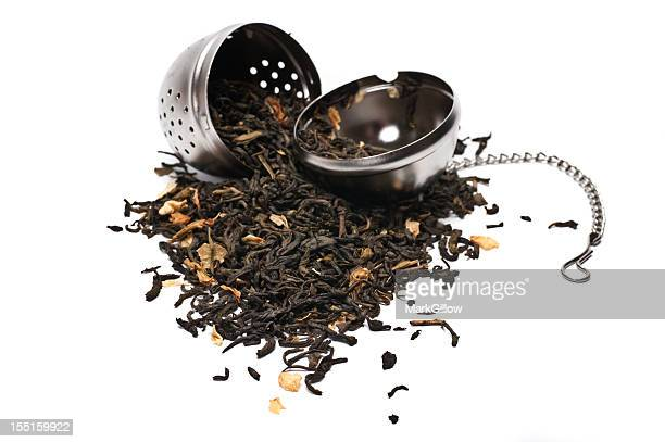 Tea leaves spilling out of a metallic tea strainer