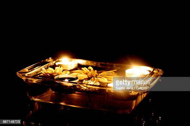 Tea Light Candles Floating On Water In Container