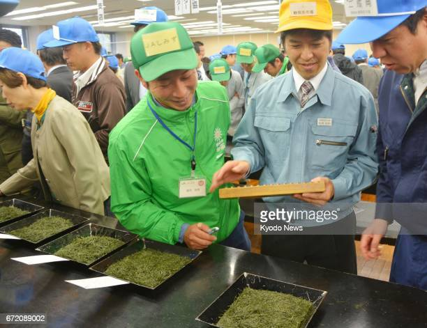 A tea market staff member holding an abacus mediates negotiations between a buyer and a seller during the first auction of the season's new green tea...
