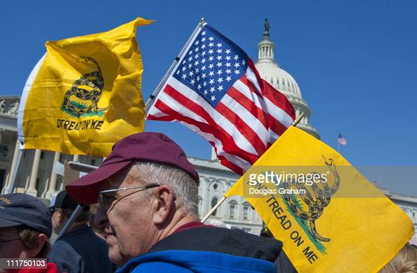 Tea party activist on the East Front of the US Capitol hold up signs and flags during a rally on Wednesday April 6 days before a possible federal...