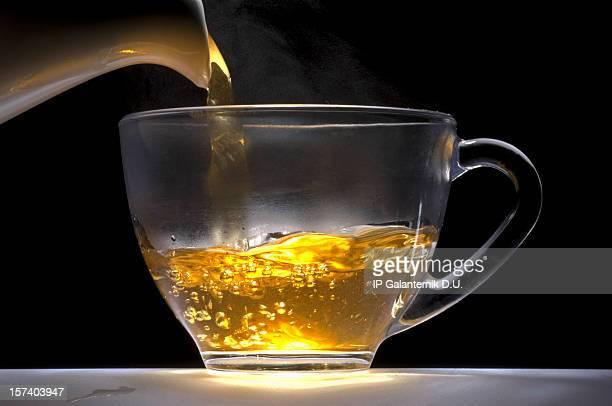 Tee eingießen von weißem Porzellan pot in Glas-Tasse.