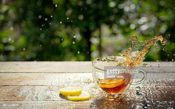 Tea splashing from glass cup, fallen lemon slice