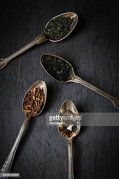 Tea spoons of Sencha, Gyokuro, Hojicha and Genmaicha on black background