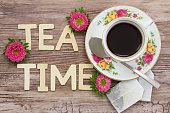 Tea time written with wooden letters, tea in vintage cup, tea bags and pink daisies