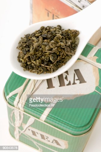 Tea tin and porcelain spoon full of green tea leaves, close up : Stock Photo