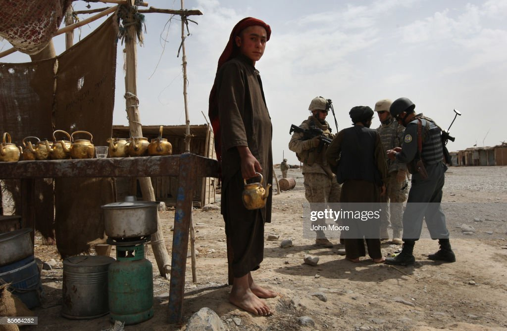 A tea vendor stands by as policeman searches a man during a joint patrol between Marines and Afghan police at an outdoor bazaar on March 27, 2009 in Delaram in southwestern Afghanistan. The Marines from the 3rd Battalion, 8th Marine Regiment based in Delaram have hightened security following two deadly suicide bomb attacks in the last two weeks there that killed four Afghan policemen and one U.S. Marine.