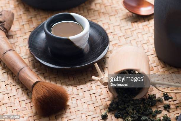 Tea whisk, mug with dried green tea leaves and cup of tea, China