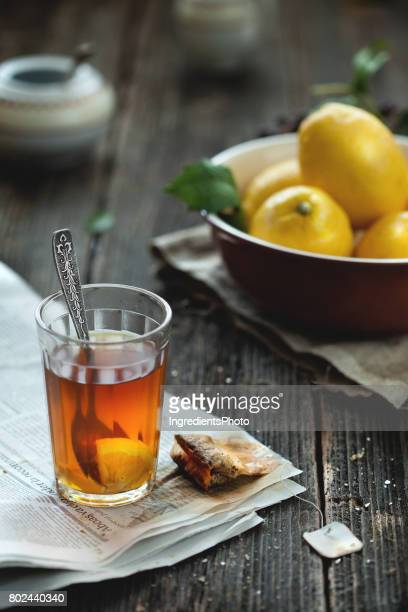 Tea with lemons in a brown bowl on wooden table.