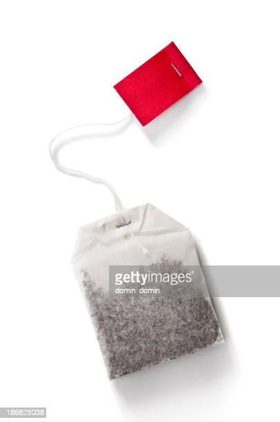 Sachet de thé avec étiquette rouge isolé sur blanc